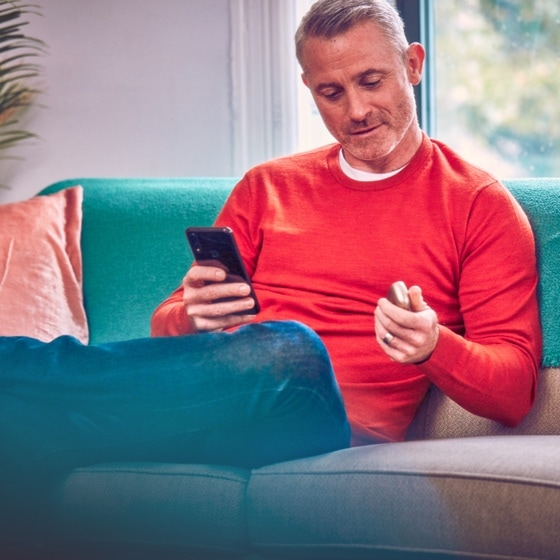 Man with phone in one hand, IQOS device in the other